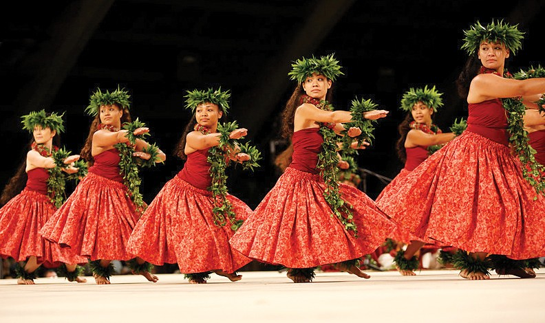 A photo of female hula dancers of the Wahine Kahiko division, mid-performance at the Merrie Monarch Festival.