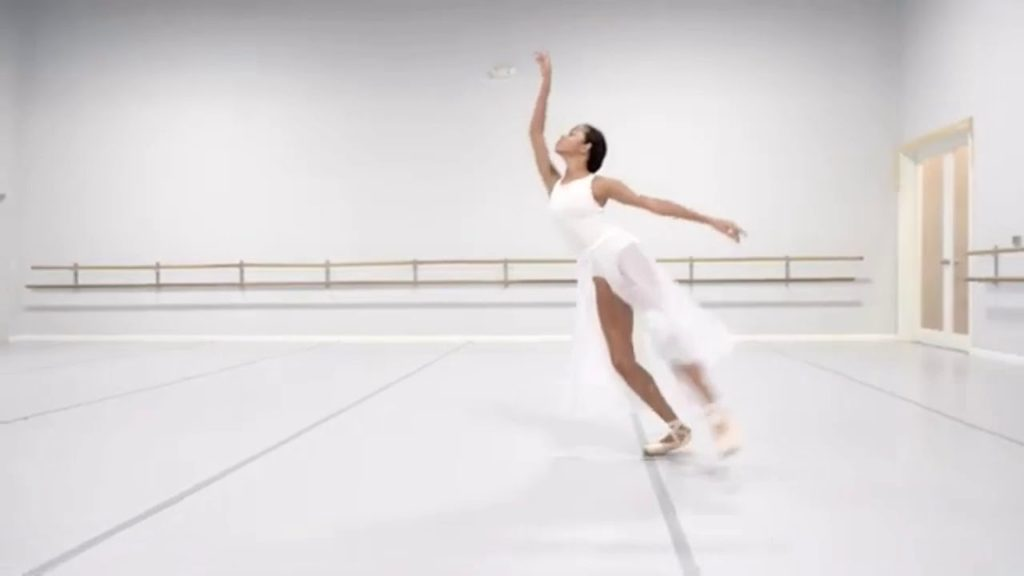 A photo of Ballerina Mia in a white flowing costume, mid-performance in a dance studio.
