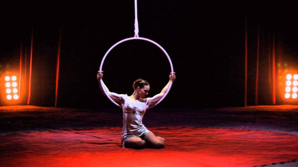 A photo of aerialist Chloe Gardiol sitting on the ground, holding her hoop above her head.