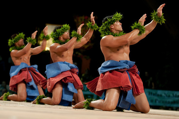 A photo of three dancers from Ke Kai O Kahiki, mid-performance onstage, on their knees with their hands raised in the air to the right.