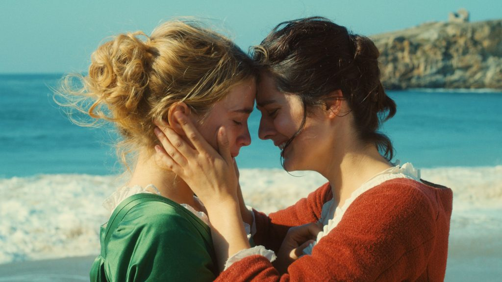 A photo still from the film Portrait of a Lady on Fire. The photo is a close up of Marianne and Héloïse with their foreheads touching, on the beach, with the ocean in the background.