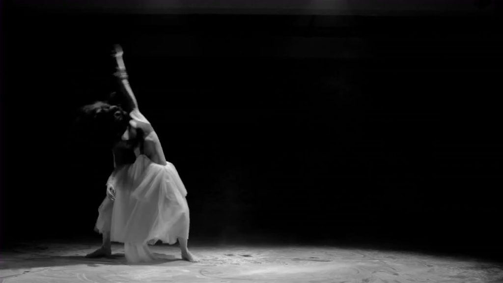 A black and white photo of dancer Shireen Talhouni, mid-performance, with an arm extended above her that is moving so fast it is blurred in the photo.
