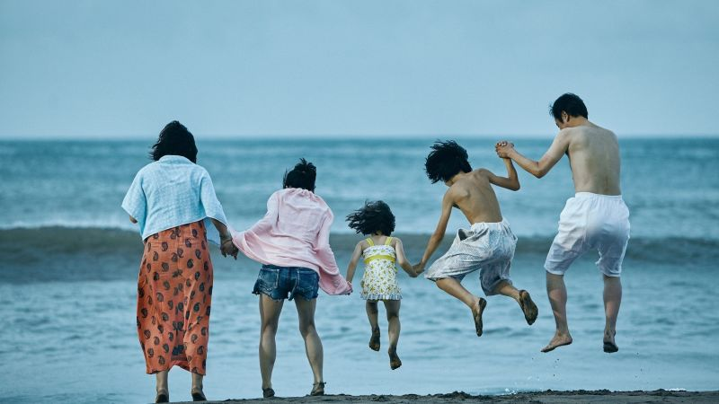 A photo still from the movie Shoplifters, taken from behind, of the main family all holding hands and jumping into the water at the beach.