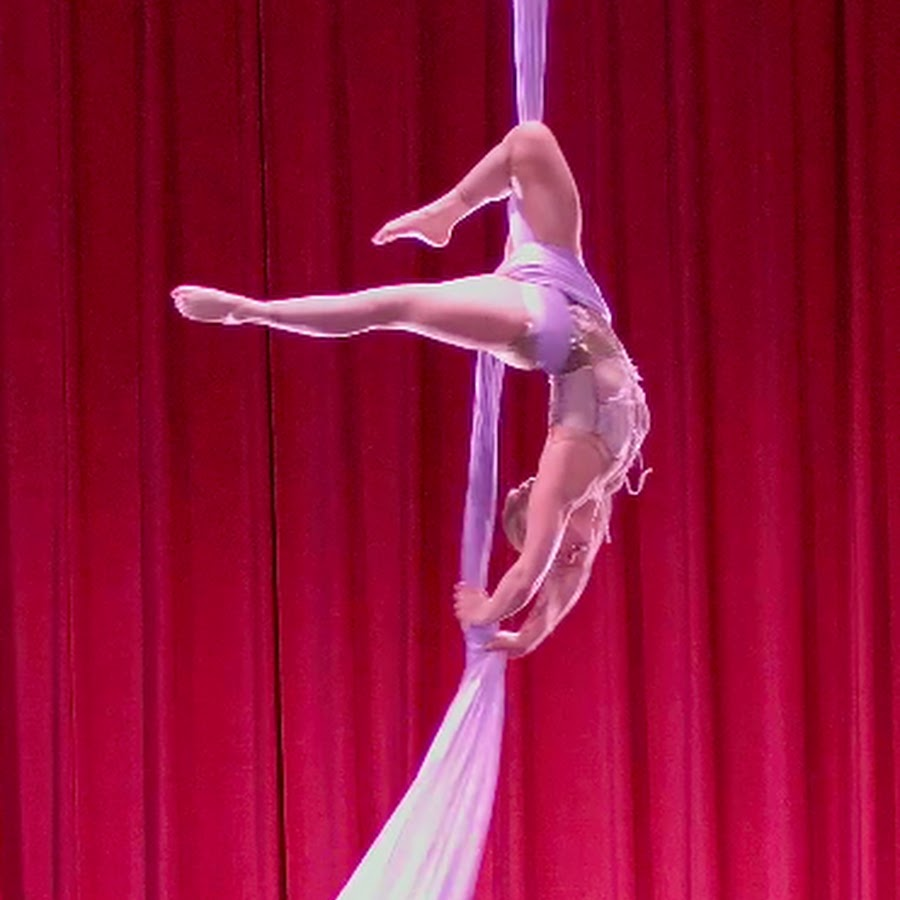 A photo of aerialist Anne Smith, mid-performance, upside down with her legs extended to the side, hanging from a set of purple silks.