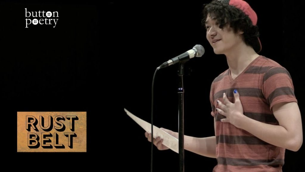 A photo of poet Spencer Brownstein mid-performance, standing onstage in front of a mic, holding a piece of paper in one hand and holding his other hand over his heart.