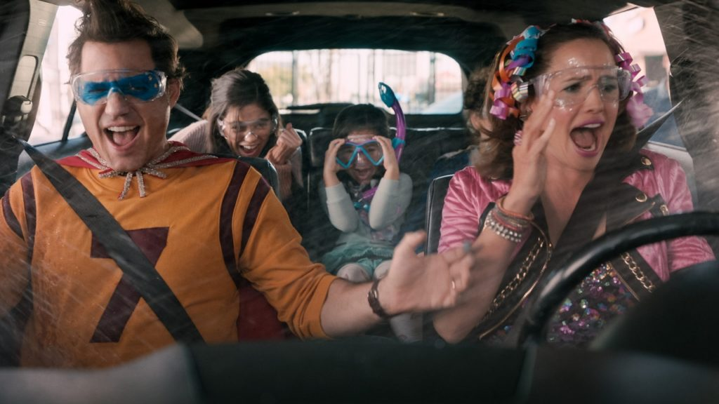 A photo still from the movie Yes Day, showing a family in a car, all dressed in outrageous outfits, going through a carwash with the windows down and getting soaking wet.