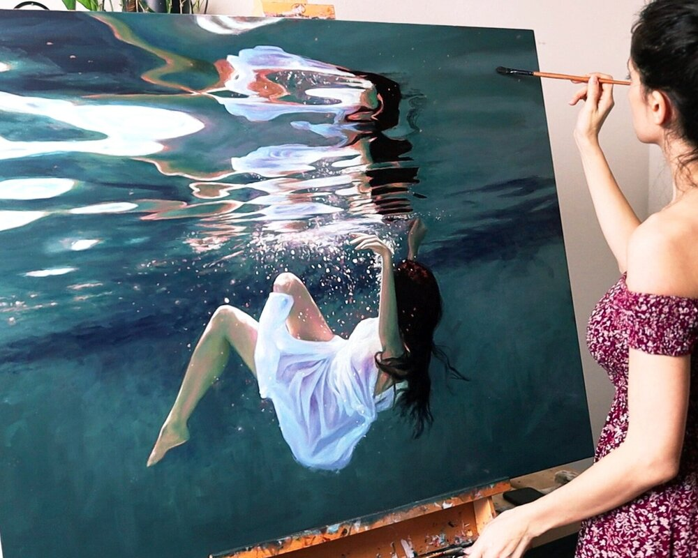 A photo of Lena Danya, standing in front of a painting on an easel, paint brush raised. The painting is of herself in a white dress, submerged underwater.