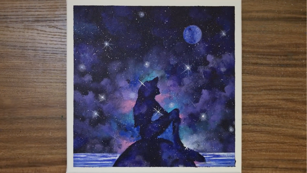A photo of the finished painting by Serena Art of the Little Mermaid. Ariel is sitting on a rock in the ocean, in silhouette, looking up at the night sky.