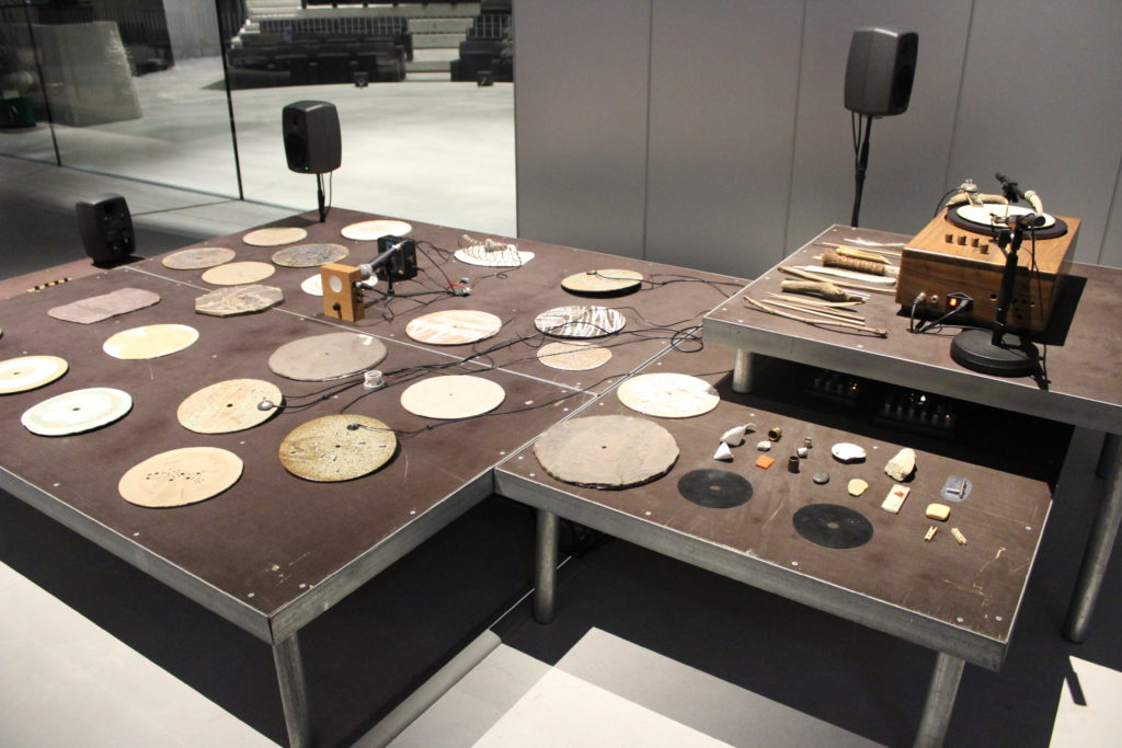 A photo of artwork The Ground by Tarek Atoui. The photo is of various instruments, plates, and sound systems on a raised platform.