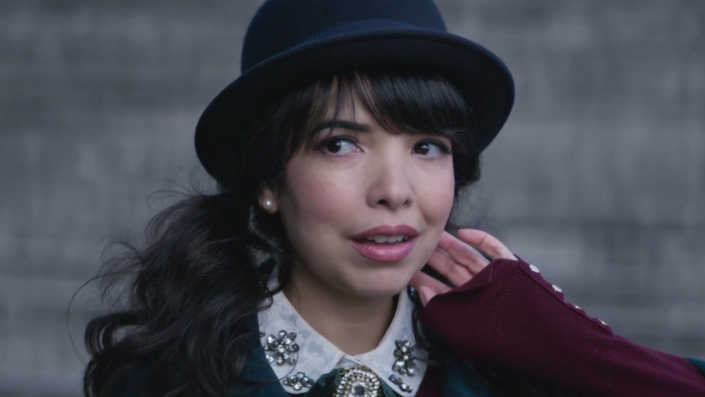A close up photo of singer Indila wearing a bowler hat in the music video for Parle à ta tête.