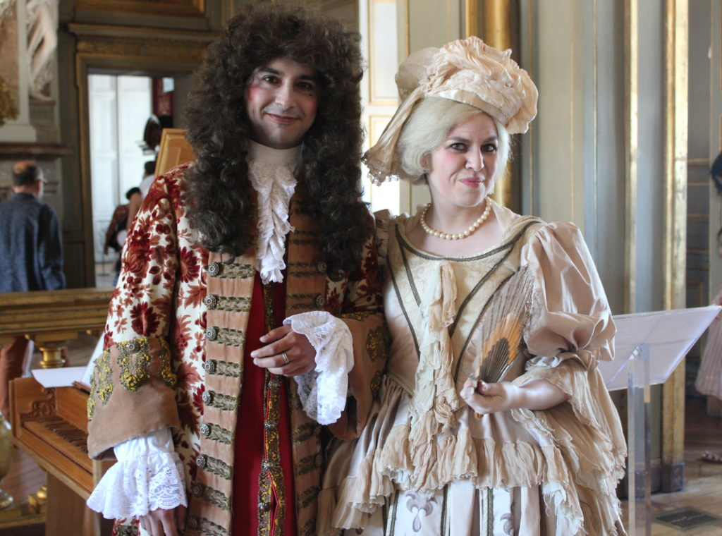 A photo of the opera singer and harpsichord player in the grand hall of the Château de Maisons. They are both wearing period piece costumes and wigs, and are smiling and posing for the camera.
