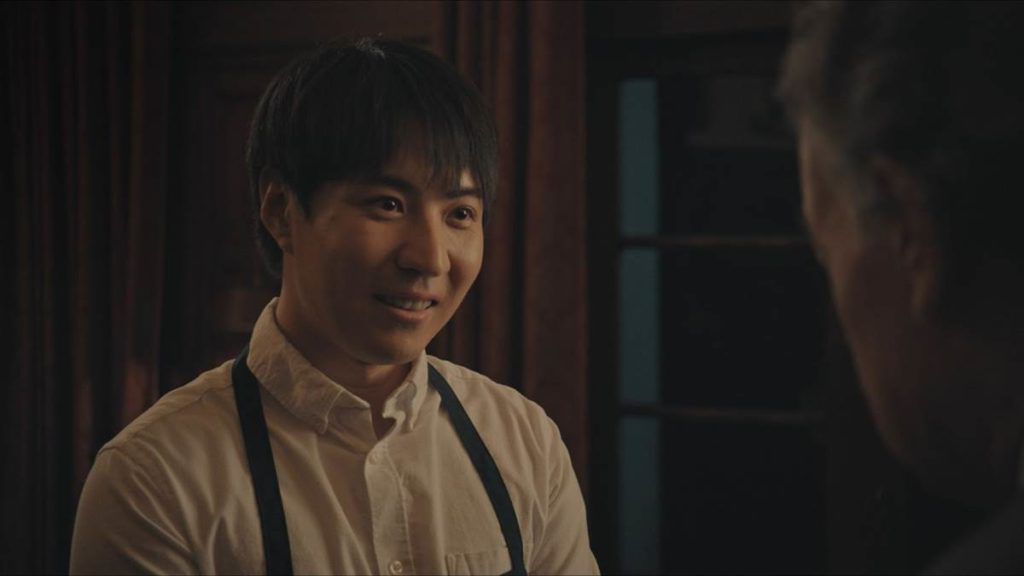 A photo still from the short film Dinner is Served. The photo is a close up of lead actor Qi Sun smiling at another character just out of frame.