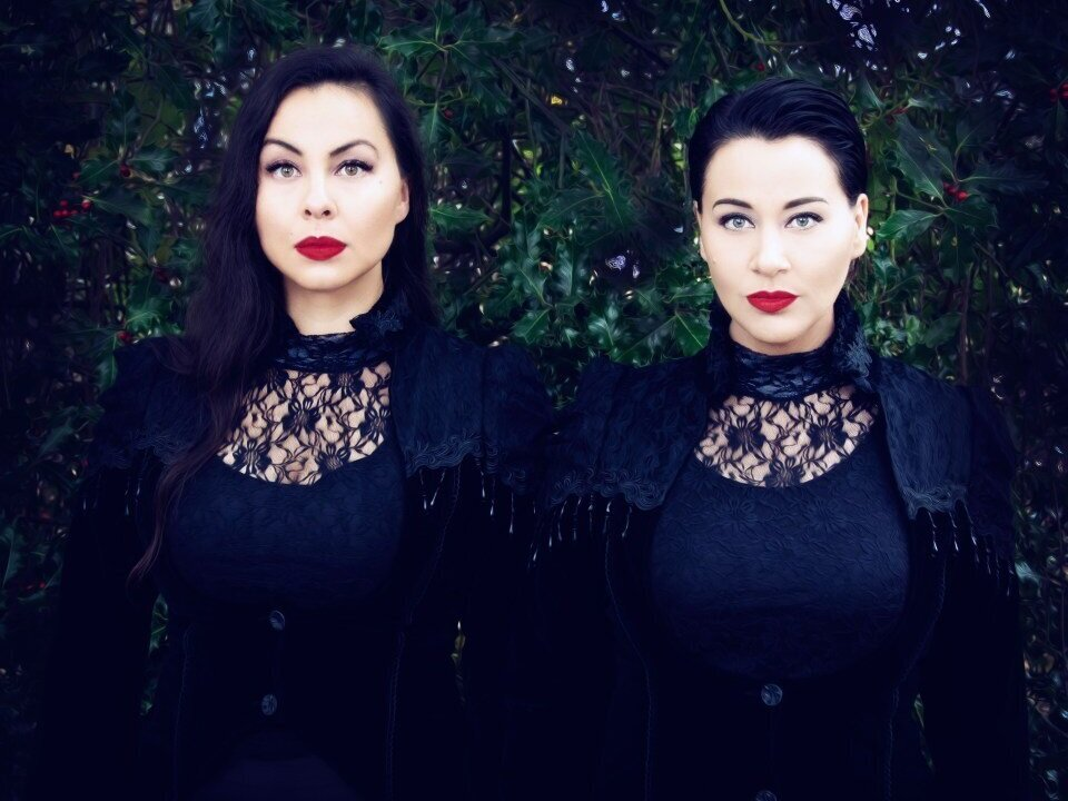 A promotional photo of Inuksuk Mackay and Tiffany Ayalik of the musical duo PIQSIQ. They are standing side by side and staring straight into the camera.