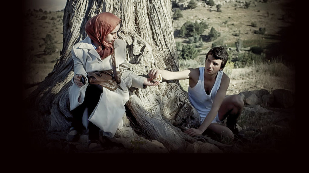 A photo still from the short film Besieged Bread. A woman and man are sitting under a tree, sharing a piece of bread.