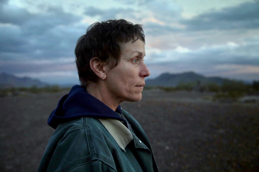 A photo still from the film Nomadland. It shows a close up of lead actress Frances McDormand, standing in a rural setting, looking off camera.