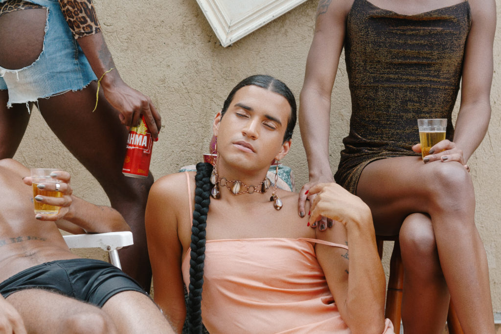 A photo from the series Carioca, Negro & Queer by Rodrigo Oliveira. The photo centres on a Black, LGBTQ individual sitting with their eyes closed. Three other Black, LGBTQ individuals sit around them with their faces out of frame.