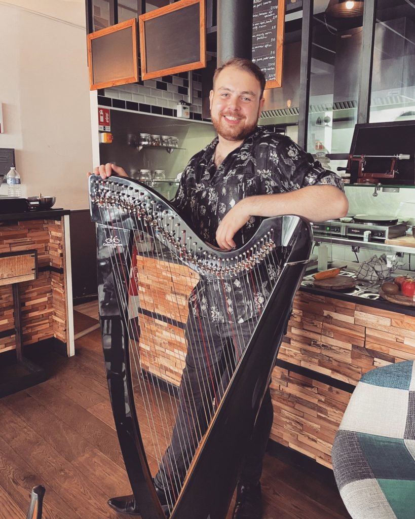A photo of the musician Stiof, arm casually resting on his harp, standing in a bar and smiling directly into the camera.